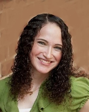 Headshot of girl with curly brown hair wearing a green shirt