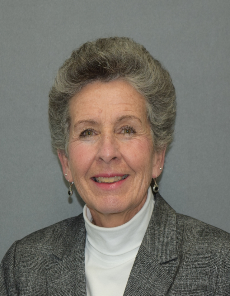 a woman with short grey hair, white turtle neck shirt and a grey blazer.